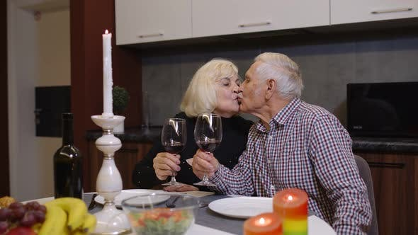 Thumbnail for Portrait of Senior Old Couple Toasting Wine at Home During Romantic Supper in Kitchen at Home