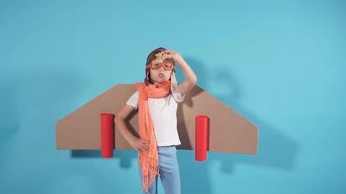 Joyful Kid Wearing Plane on Back Isolated Over Blue Background