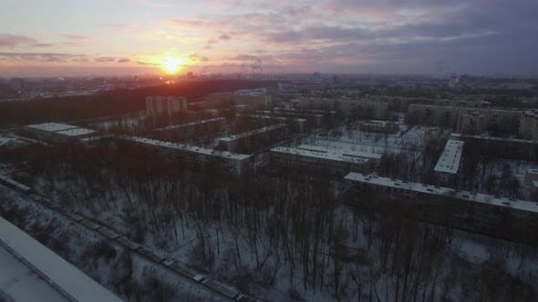 Flying over winter city and moving cargo train St Petersburg scene at sunrise