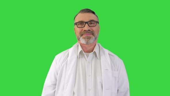 Mature Doctor Listening To Someone Behind the Camera and Smiling on a Green Screen Chroma Key