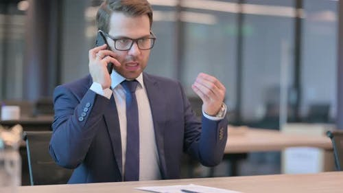 Angry Businessman Talking on Phone in Office