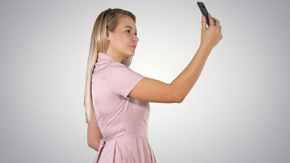 Thumbnail for Young beautiful woman makes selfie on her phone on gradient