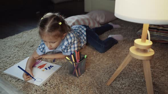 Girl Child Draws Colored Pencils On Paper Picture In Interior