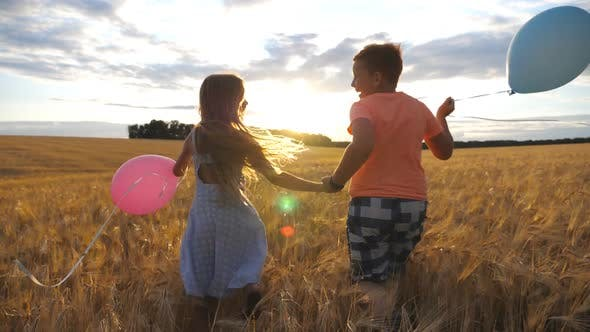 Thumbnail for Couple of Little Kids with Balloons Running Through Wheat Field, Turning To Camera and Smiling