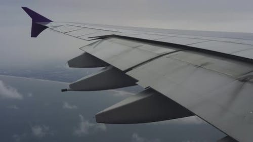 Wing of airplane flying above the sea