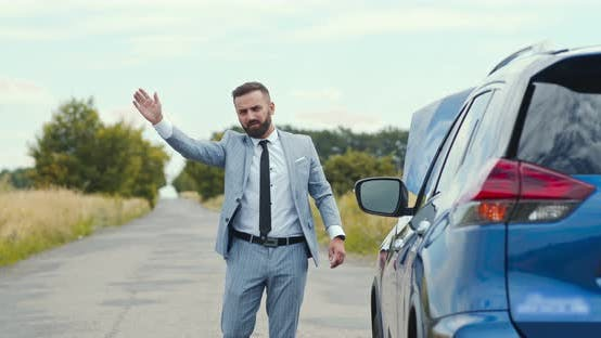 Thumbnail for Businessman Standing on Road Near Broken Car and Trying To Catch Help, Countryside Background