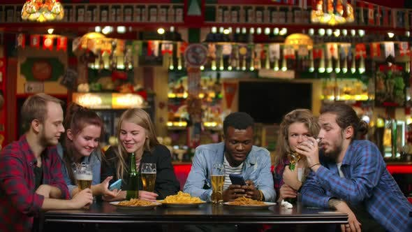 Thumbnail for Cheerful Students Sitting at a Table in a Bar Drinking Beer, Eating Chips and Watching Photos on a