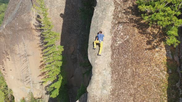 Aerial Shot of a Young Man Carefully Climbing a Rock Wall Without a Safety Net