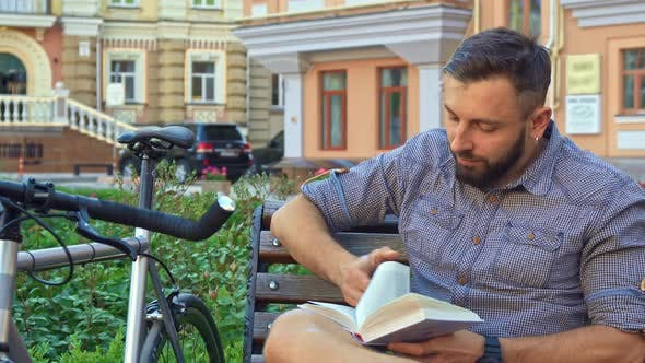 Thumbnail for Cyclist Turns the Page of the Book on the Bench
