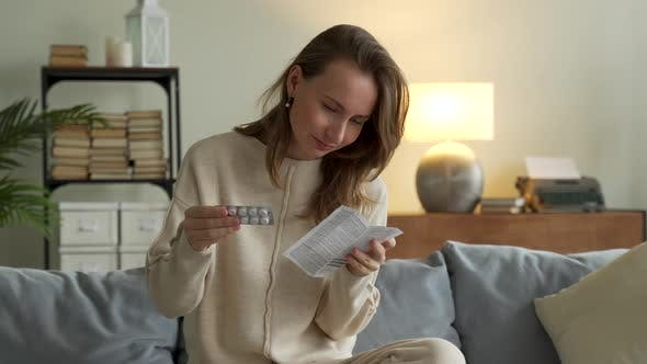 Woman Reading Leaflet Before Take Pill Sitting Couch Living Room Home
