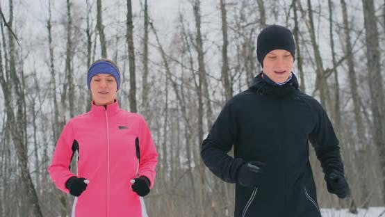 Thumbnail for A Man and a Woman in a Pink Jacket in the Winter Running Through the Park