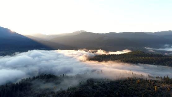 Flying Toward Sun Rising Above Ridge Across Fog Covered River Landscape