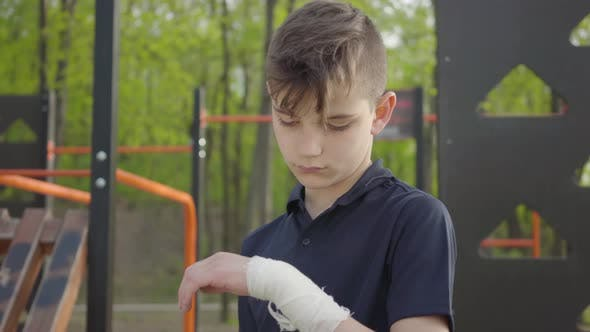Cover Image for Young Boy with Bandaged Hand in the Playground. Kid Want To Play but He Is Injured