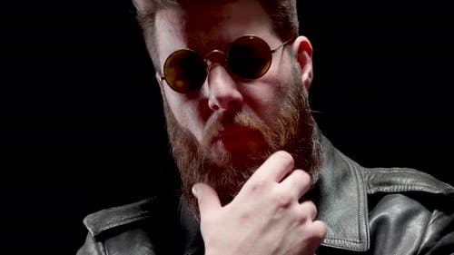 Serious Man with Heavy Metal Look Chews Tabacco and Touches His Beard