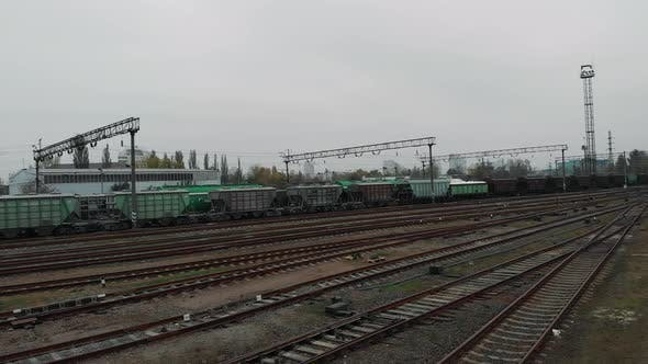 Aerial view of long freight cargo train with wagons and fuel tanks