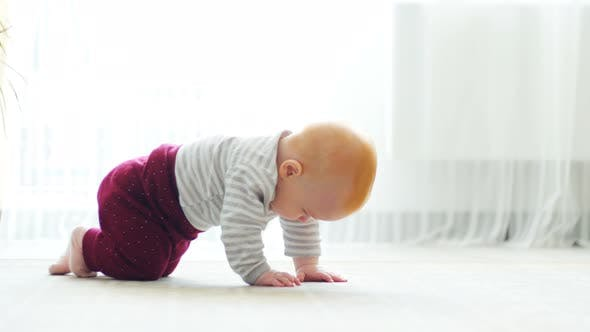 The Baby Girl Learns To Crawl, the First Attempts To Crawl. Baby Crawls To the Camera, Smiling and