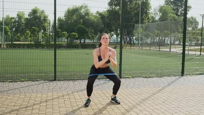 Young Sporty Woman Performs a Squat with an Elastic Band