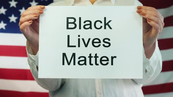 Thumbnail for Woman Holds Poster Black Lives Matter on American Flag Background
