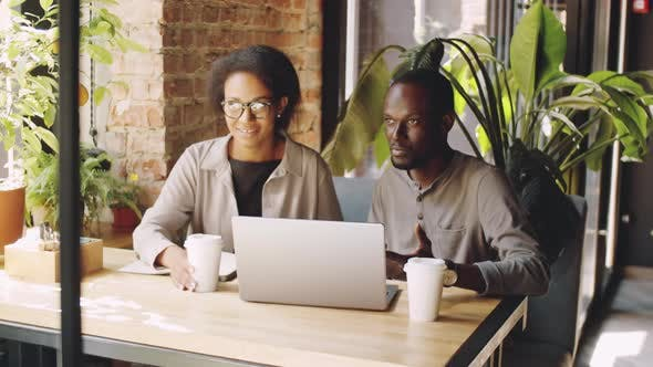 Thumbnail for Black Man and Woman Discussing Business Project on Laptop in Cafe