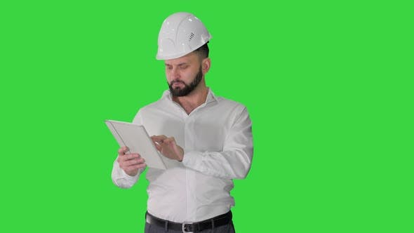 Construction Specialist Using a Tablet Computer While Walking on a Green Screen, Chroma Key.