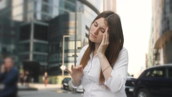 Thumbnail for Tired Businesswoman Having Headache in the Business Part of the City. A Woman Sits and Massages the