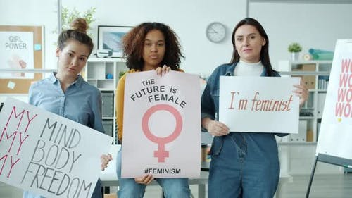 Confident Ladies Multiethnic Group Holding Feminist Banners Looking at Camera Standing Indoors