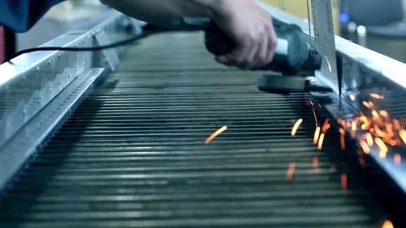 Thumbnail for Funken aus einer industriellen Schleifmaschine fallen und springen auf den Boden einer Werkstatt