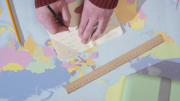Adventurer Writes in a Notebook on a Table with a Map
