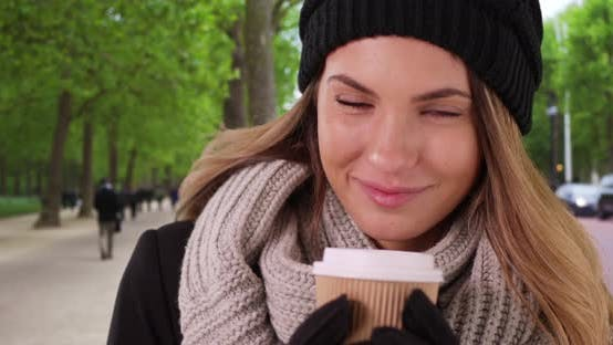 Thumbnail for Smiling woman in cozy hat and scarf holding paper coffee cup
