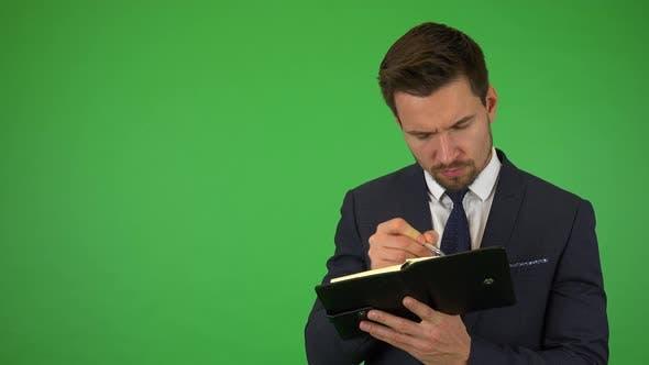 Thumbnail for Ein junger, schöner Geschäftsmann schreibt in ein Notebook - Green Screen Studio