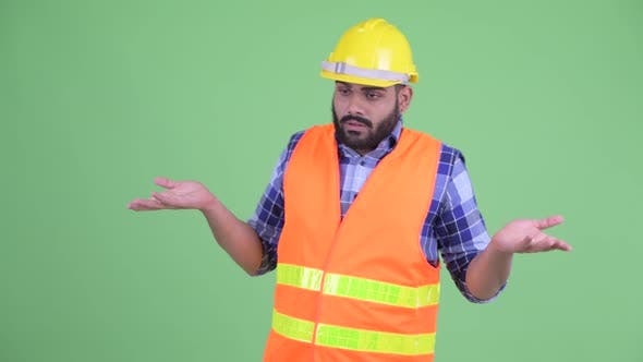 Thumbnail for Confused Young Overweight Bearded Indian Man Construction Worker Shrugging Shoulders