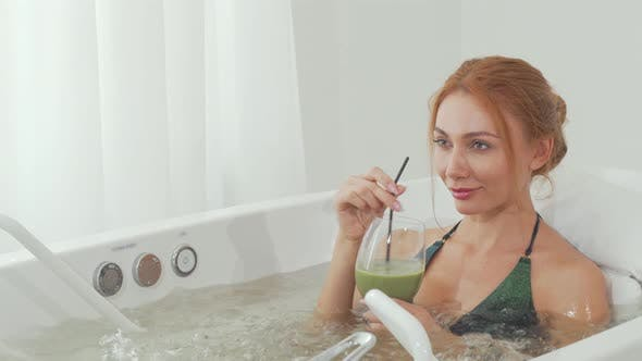 Thumbnail for Sliding Shot of a Beautiful Woman Sipping Delicious Smoothie in Whirl Pool Bath