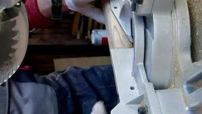 Vertical Shot Woodworker in Protective Gloves Cuts Off Piece of Wood with Mitre Saw Closeup