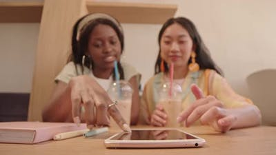 Young Women Scrolling on Digital Tablet in Cafe