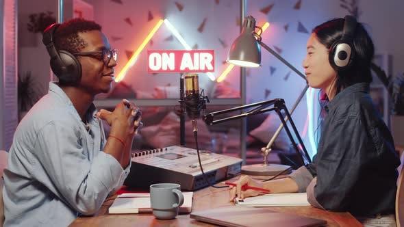 Thumbnail for Junge Diverse Radio-Moderatoren posieren für Kamera und Lächeln im Studio