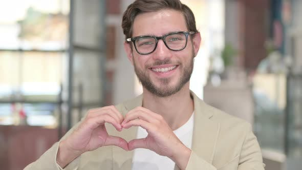 Young Man Showing Heart Sign By Hand