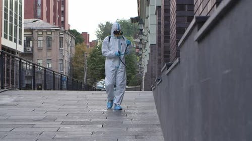 Virologist in a Protective Suit Disinfects the Surface, Sprays Liquid Chemicals on the Ground and