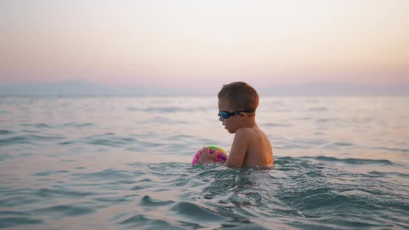 Thumbnail for Child Taking Ball To Water and Then Floating on It in the Sea