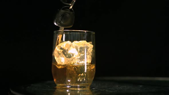 Car keys falling in tumbler of whiskey