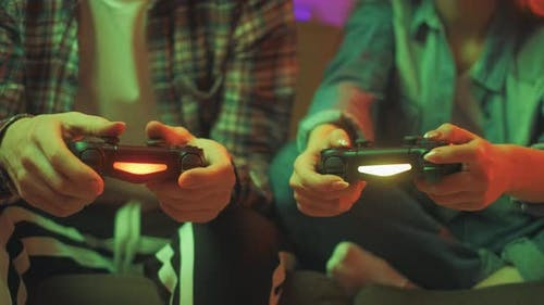 Hands of a Man and Girl Holding a Joysticks To Play Video Games on TV