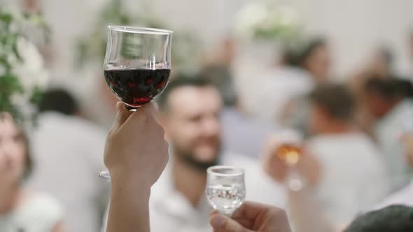 Closeup. Glasses Hands While Doing Cheers Celebrate in a Restaurant, Set Table Blurred Background