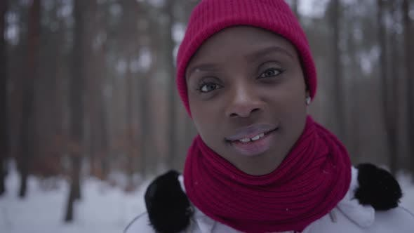 Thumbnail for Portrait Cute Smilling African American Girl Wearing a Red Hat and a Red Scarf Standing in Winter