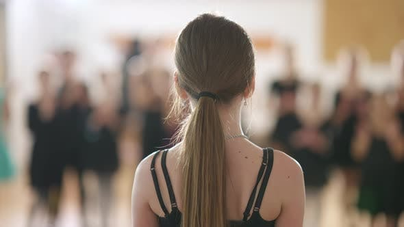 Back View Closeup of Caucasian Girl Standing in Dancing School with Blurred Children Clapping at