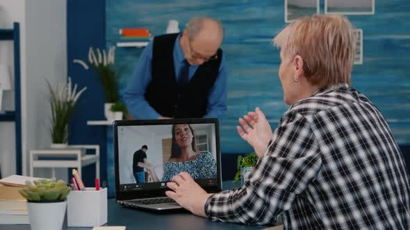 Middle Aged Woman Talking Video Conference with Children