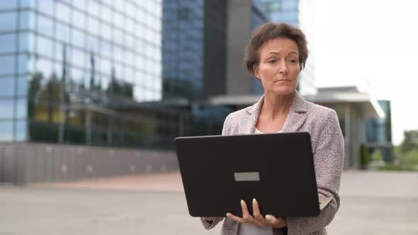 Thumbnail for Mature Beautiful Businesswoman Using Laptop In The City Outdoors