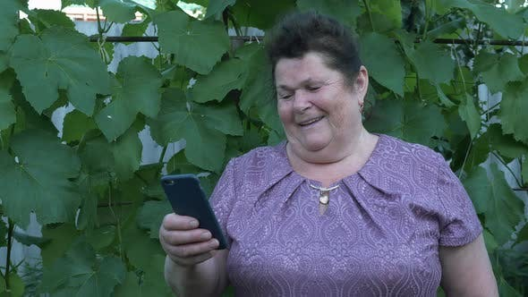 Thumbnail for Happy smiling 80 year old senior woman with modern smartphone in hands.