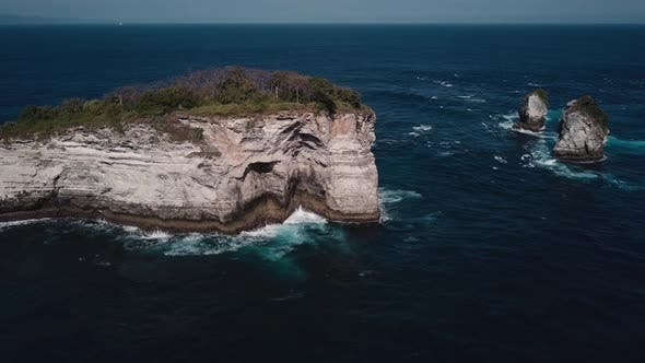 Thumbnail for Aerial Shot of Waves Crashing on Small Tropical Rocky Island on the Coast