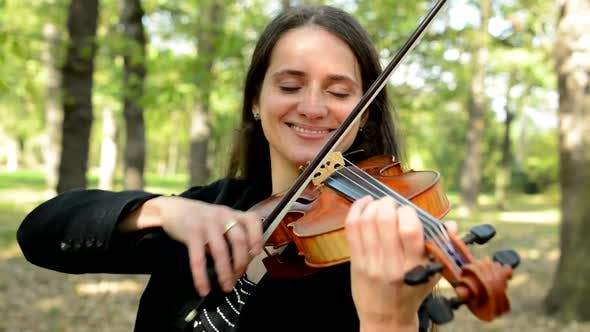 Thumbnail for Young Attractive Happy Woman Plays on the Violin in the Park
