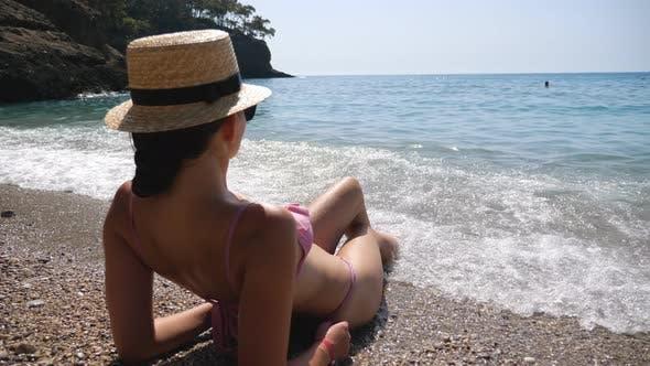 Sexy Woman Lying on Beach and Sunbathing Enjoying Sea Waves