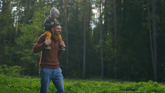 Thumbnail for Slow Motion: Son Sitting on His Fathers Neck in the Spring Sunny Park. Fathers Day. Father and Boy
